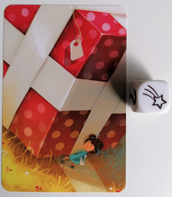 Izquierda, una carta que muestra: Una niña pequeña intenta levantar una pesada y enorme caja, envuelta en papel de regalo rojo con cinta blanca.  Derecha, un dado mostrando en su cara superior: una estrella fugaz.