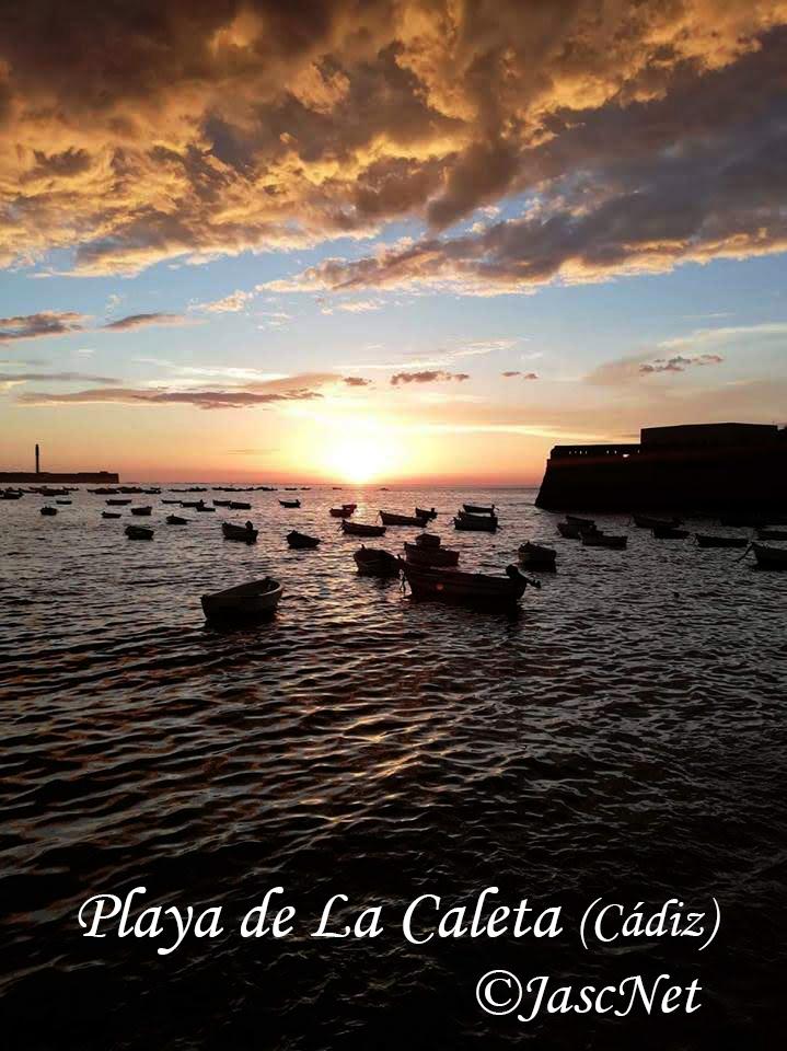 """Fotografía de una puesta de sol en la playa de """"La Caleta"""", Cádiz. El sol se oculta entre las nubes, que tapan la parte superior de la fotografía, y el mar, dónde se balancean varias barcas. A los lados, el Castillo de San Sebastián, a la izquierda, y el de Santa Catalina, a la derecha."""