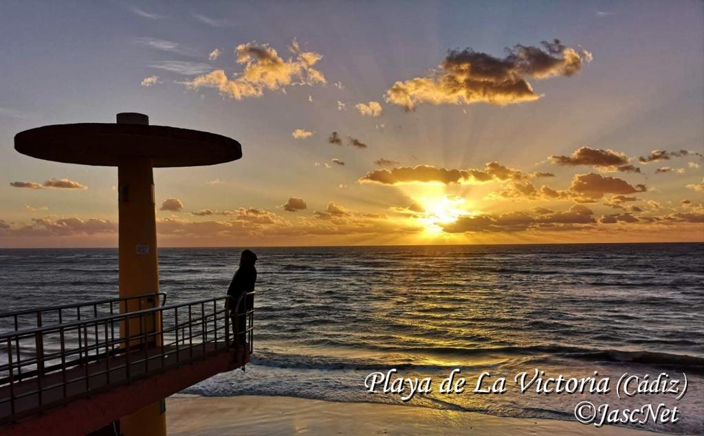 Fotografía de una preciosa puesta de sol en la playa de La Victoria, Cádiz. A la izquierda de la foto se puede ver parte de la escalinata de bajada a la playa y a la derecha el sol ocultándose entre las nueves y el horizonte.