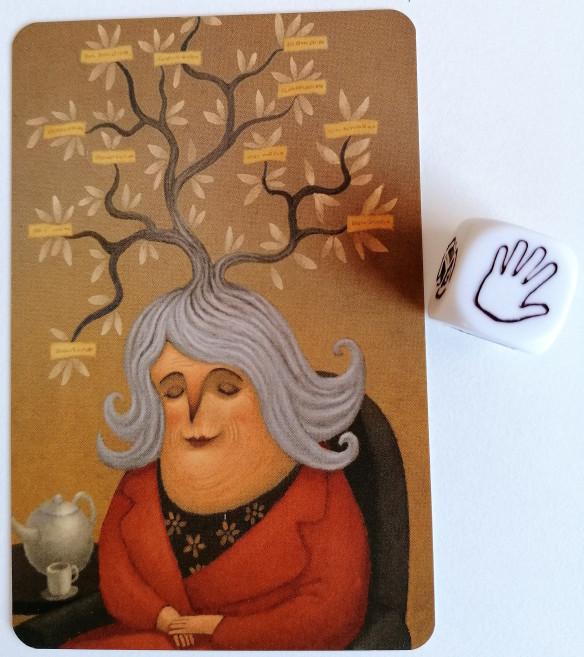 Imagen que muestra la carta y el dado propuesto para el reto. En el dado aparece una mano y en la fotografía, una señora de pelo blanco que dormita sentada en una silla junto a una mesita con una tetera y una taza. De su cabeza sale algo parecido a un árbol y en cada rama unos cartelitos.