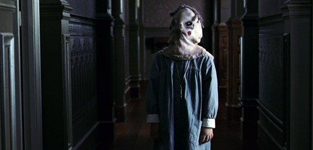 """Fotograma de la película """"El Internado"""" en dónde se ve a uno de los niños protagonistas, con un babi y la cara tapada con un saco que lleva pintado ojos y boca."""