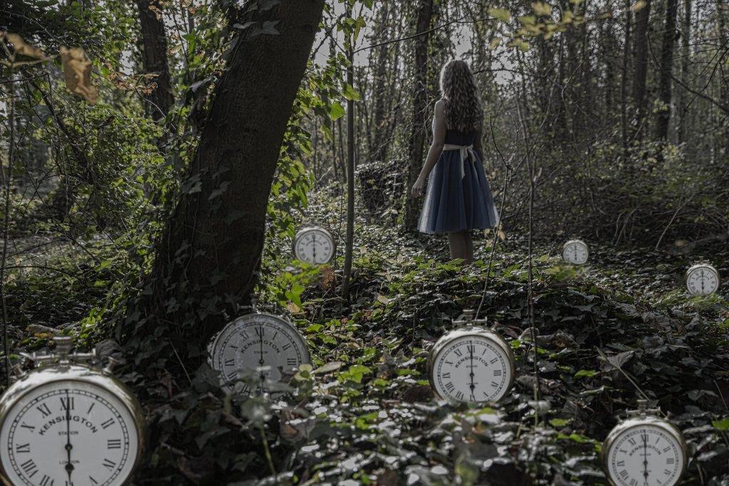 Imagen base para la inspiración. Una chica, de espaldas y disfrazada como Alicia en el país de las Maravillas, está en un bosque y en el suelo aparecen varios relojes, tipo despertador. Todos señalan las seis en punto.