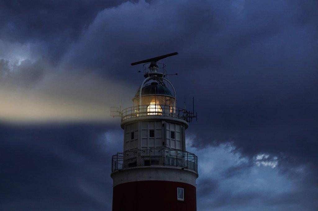 Fotografía de la parte superior de un faro, inmerso en un cielo lleno de nubes grises. La apariencia es la de una luz dentro de una tormenta.