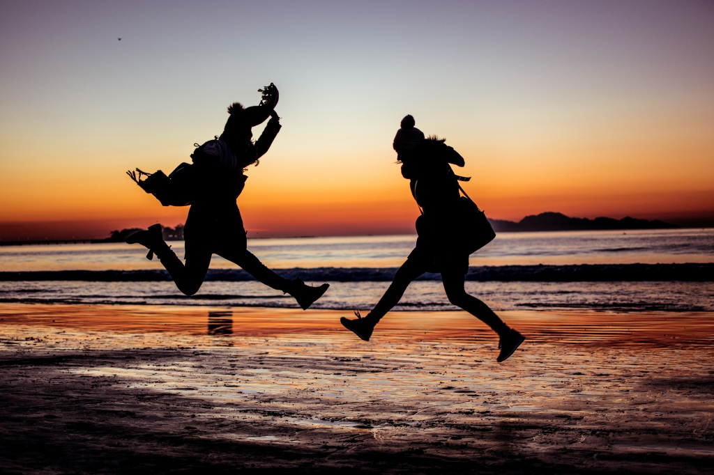 Dos jóvenes saltan de alegría en la orilla de una playa. Solo se ve sus siluetas, teniendo como fondo una puesta de sol, donde ya se ha escondido el astro. La imagen es una típica fotografía a contraluz donde las siluetas toman el protagonismo en el centro.