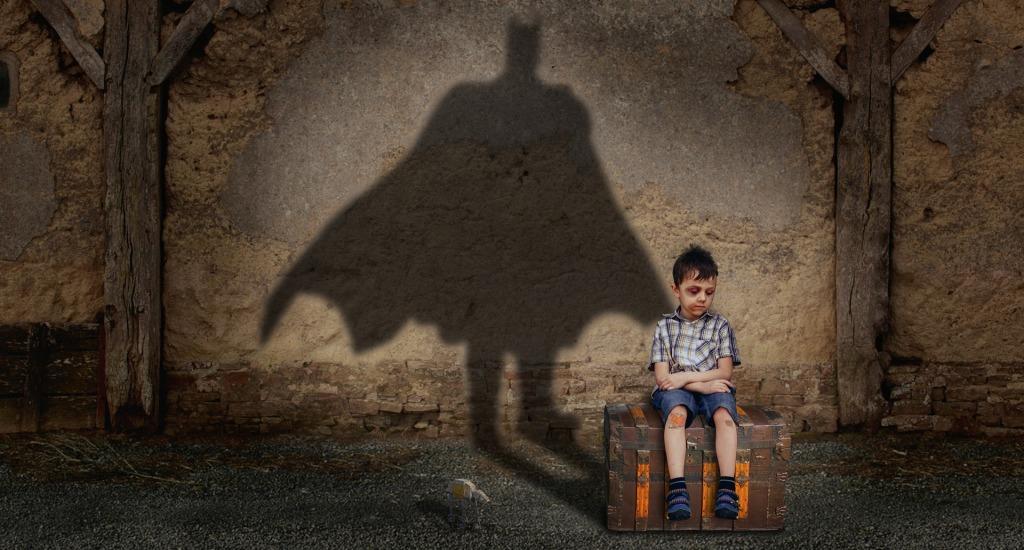En la imagen se puede ver a un niño, de unos siete u ocho años, sentado encima de un cofre-baúl. Tiene la cara y las rodillas magulladas, posiblemente por una pelea o maltrato. Desde dónde está, proyecta sobre la pared, tras él, una sombra con la silueta de Batman. La escena se presenta en un ambiente triste, solitario y el niño muestra cara pensativa.