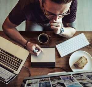 Un hombre en actitud pensativa sentado frente a un ordenador. A un lado tiene un cuaderno y un lápiz, una taza de café y un pastel de manzana.
