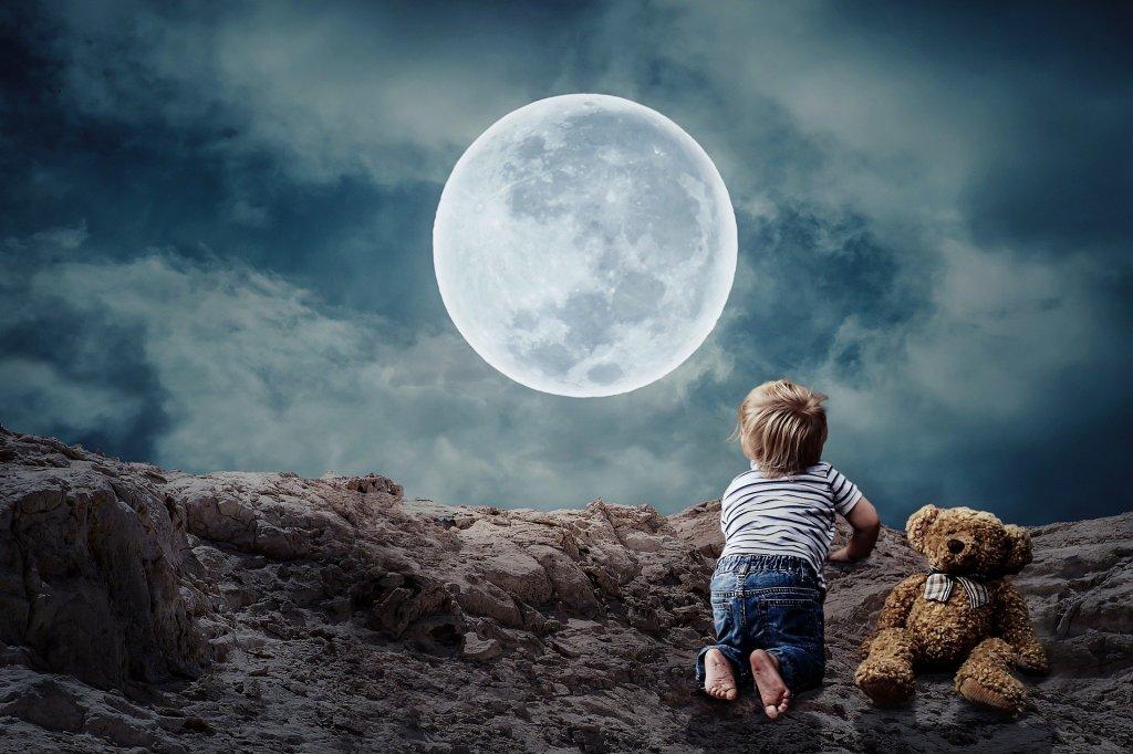 Un niño/a pequeño/a se asuma a un risco, acompañado de su oso de peluche, para contemplar una enorme y hermosa luna llena. El cielo no está todavía negro. Una neblina de nubes blancas le dan marco a la luna en un cielo azul cobalto.