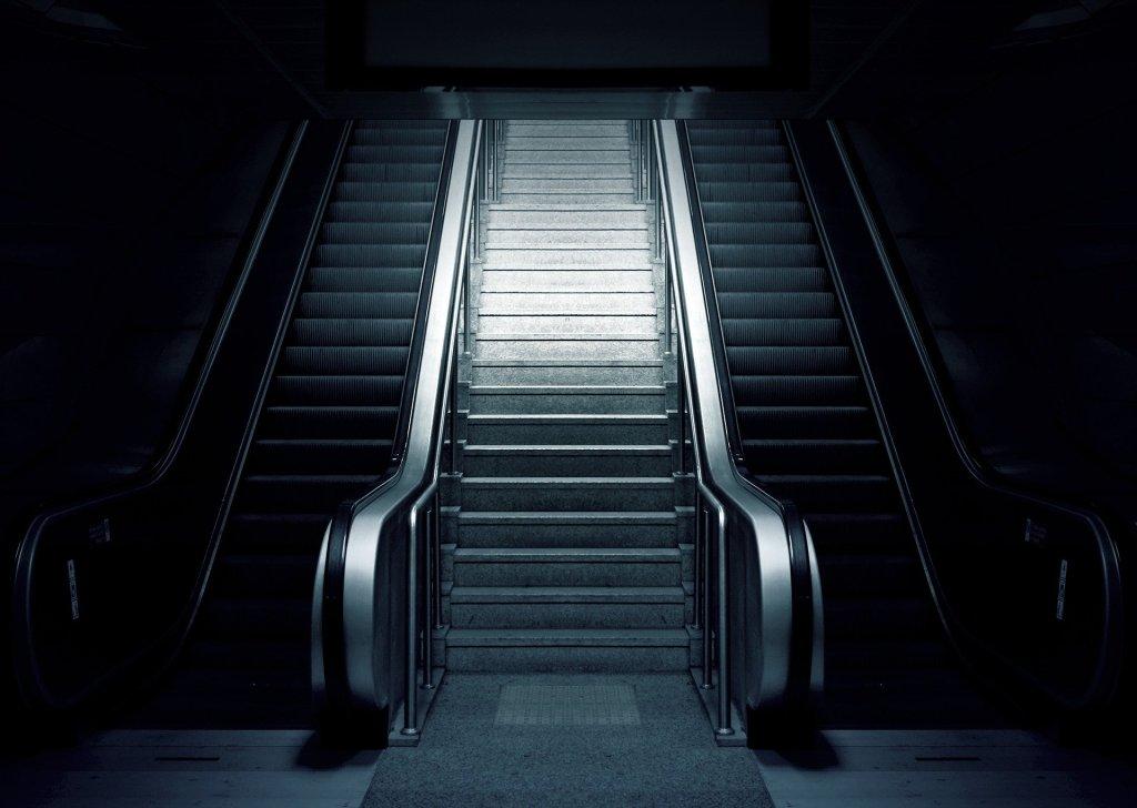Una escalera central aparece escoltada por dos escaleras mecánicas (se supone que una de subida y otra de bajada) . El ambiente es oscuro y la iluminación incide principalmente en la escalera no mecánica, dejando las otras dos en penumbra y ocultando todo el entorno.