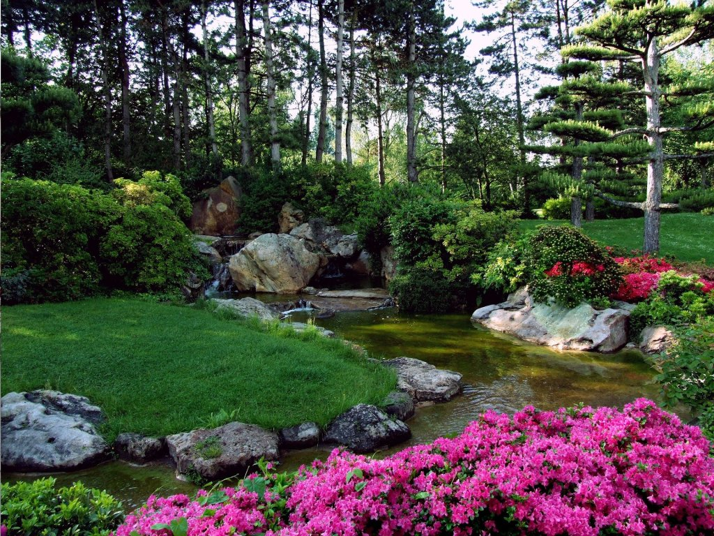 Fotografía de un parque ornamental japonés.  Un riachuelo divide la pantalla desde el centro hacia la derecha y luego hacia abajo y a la izquierda. El verde domina la zona izquierda, los árboles la parte superior y flores de color rosa la zona inferior de la fotografía. El clima de la imagen contagia serenidad y relax.