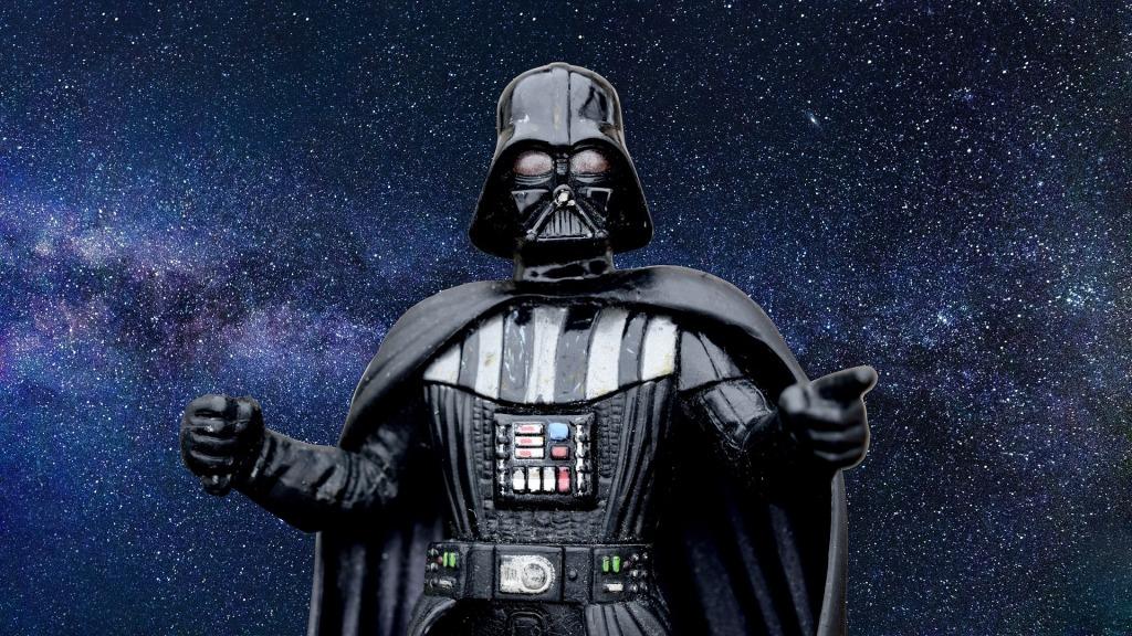 """Imagen de Darth Vader sobre un fondo estrellado. El malo de la guerra de las galaxias de toda vida. El que parece que va a una fiesta de """"emos"""". Con su casco modelo alemán, capa y esos botones en el pecho que parece un videocassette."""