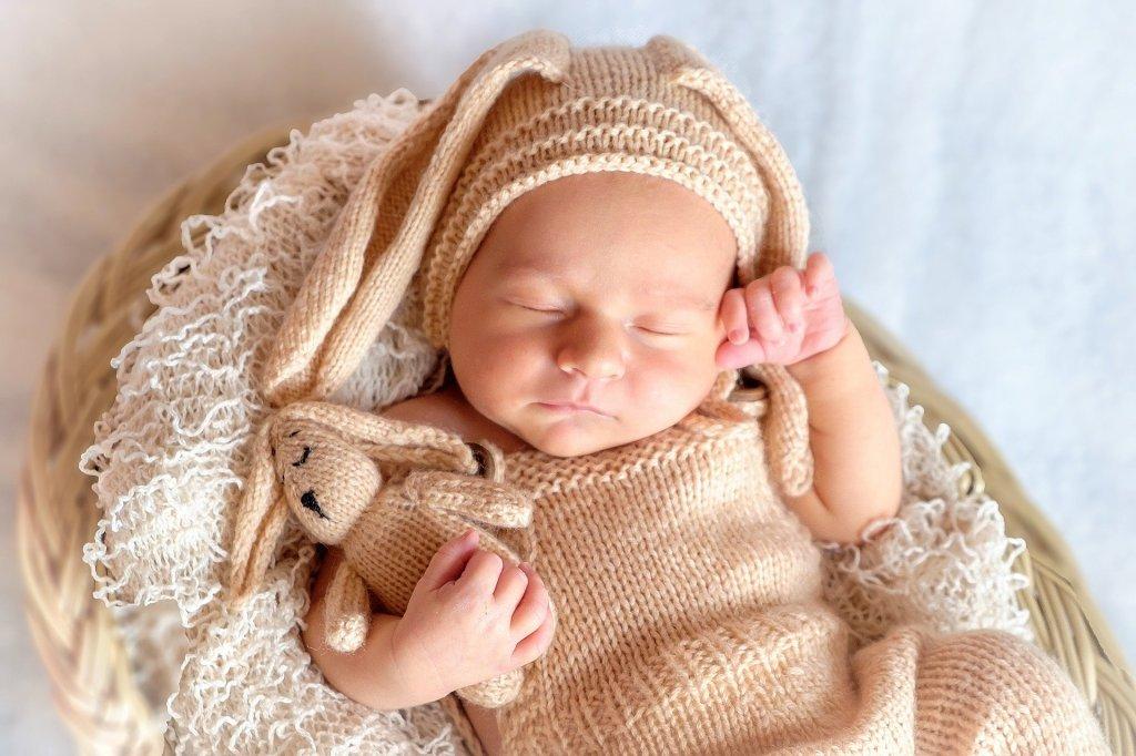 Fotografía de un bebé felizmente dormido. Un cesto de mimbre sin asa le sirve de cama y una mullida manta de hilo blanco le viene como colchón.  Va vestido con ropita de punto marrón claro y lleva un gorrito con orejas de conejo, como el muñeco que porta en su brazo derecho. La mano izquierda se apoya en su sien, generando la imagen el mayor de los placeres oníricos.
