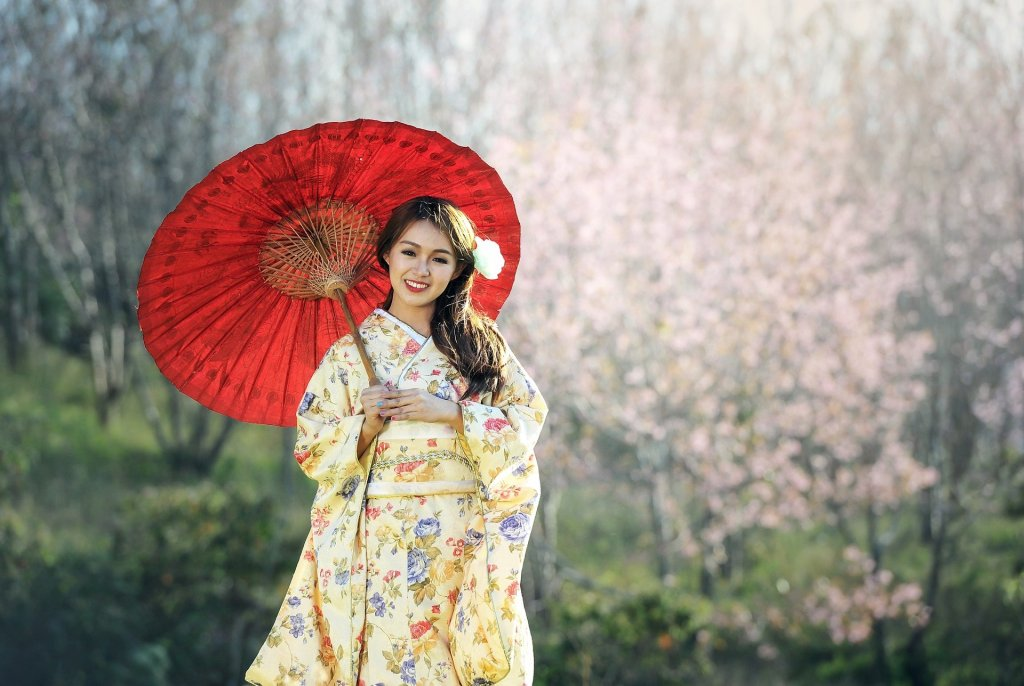 Foto de una chica japonesa, vistiendo el traje de Geisha y portando un parasol rojo. De fondo, desenfocado, varios almendros floreados.