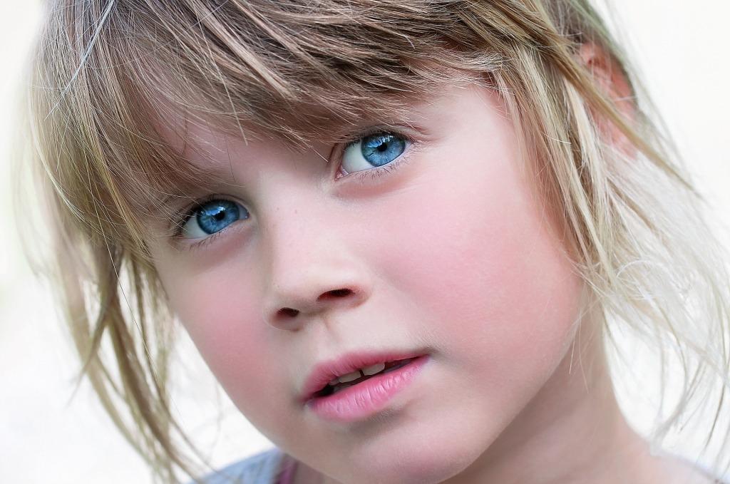 Una niña, rubia, despeinada y de ojos azul intenso. Su expresión es de duda o meditación.