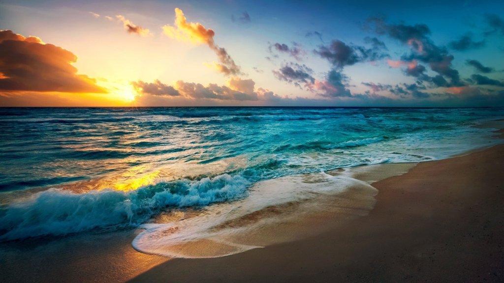 Imagen del mar llegando a la orilla de una playa. Espumoso y azul. El cielo viste muchas tonalidades de azul y amarillo, salpicado de finas nubes en el fondo.