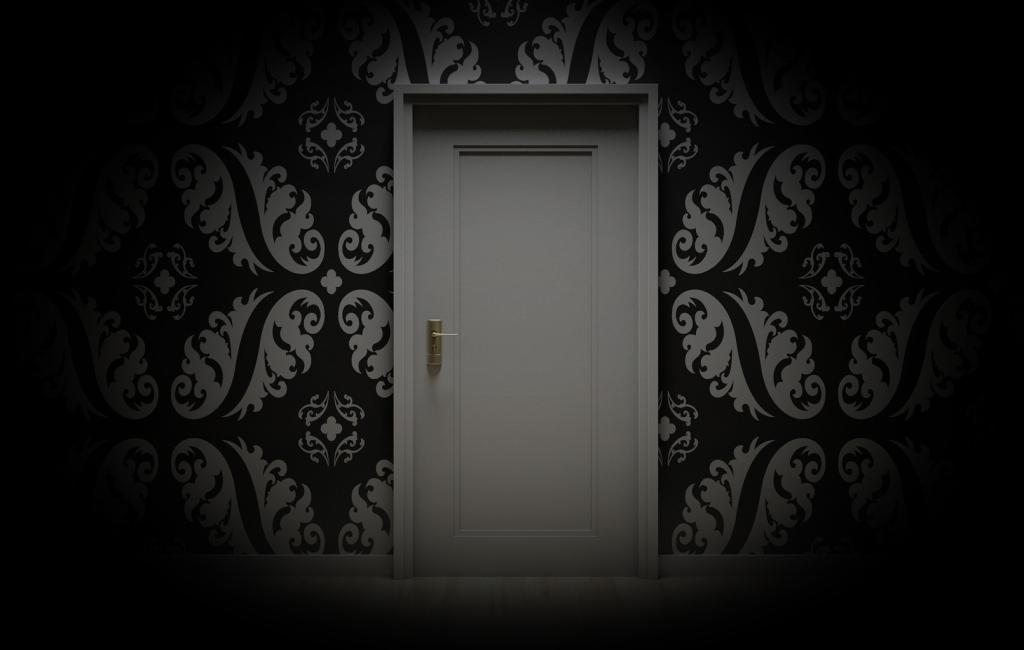 Una puerta, blanca, en un pared empapelada en tonos blancos y negros.  Creo que los motivos son ramas ornamentales. La vista simula un ojo que deja en penumbra el resto de la habitación.