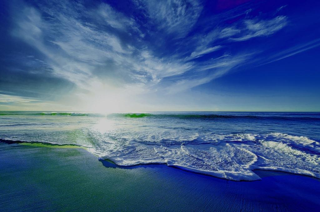 Imagen de una puesta de sol en la playa, desde la orilla. Donde se ven las olas rompiendo en la arena. El cielo crea una ligera simetría horizontal con el mar, pero cambiando las espuma de las olas rompientes por hilachas de nubes. La foto está manipulada para forzar los azules sobre los demás colores.
