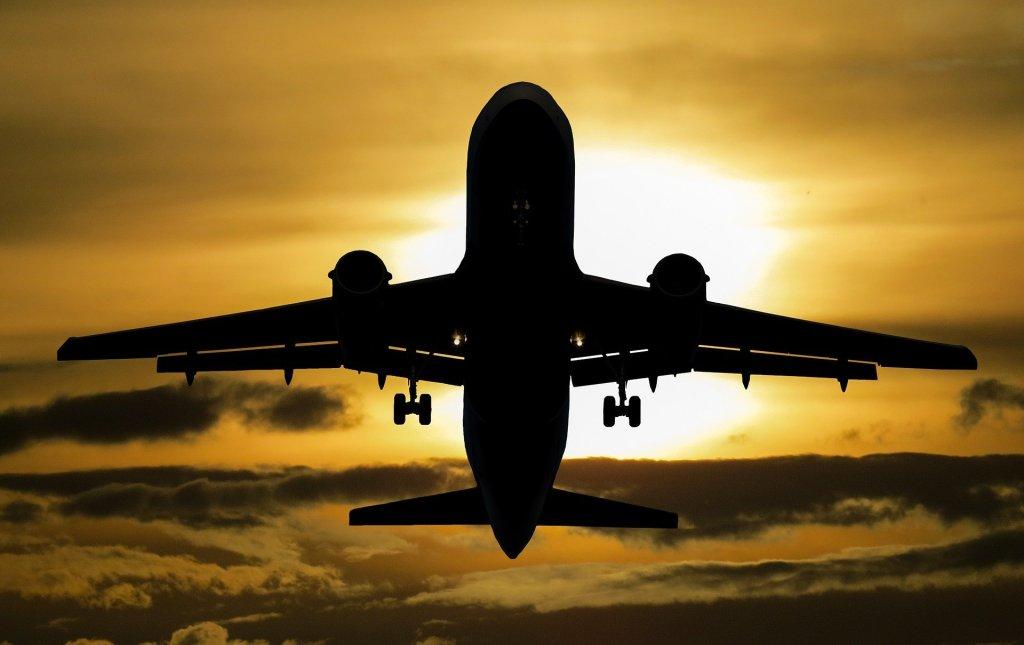 Imagen de un avión en vuelo realizada a contraluz. Se ve la silueta del aparato sobre un cielo con tonos amarrillos, predominante, y marrones, nubes. El sol está tapado por la aeronave y ésta apunta hacia arriba.