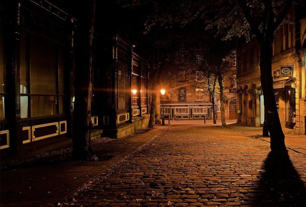 Fotografía de una calle solitaria iluminada por farolas. Solo se ve una al fondo y la que está oculta en primer plano solo se adivina por la luz que ofrece. Los árboles en las aceras se ven como sombras y el adoquinado del suelo brilla con las tenues luces. Predominan los tonos marrones y el negro de las sombras.