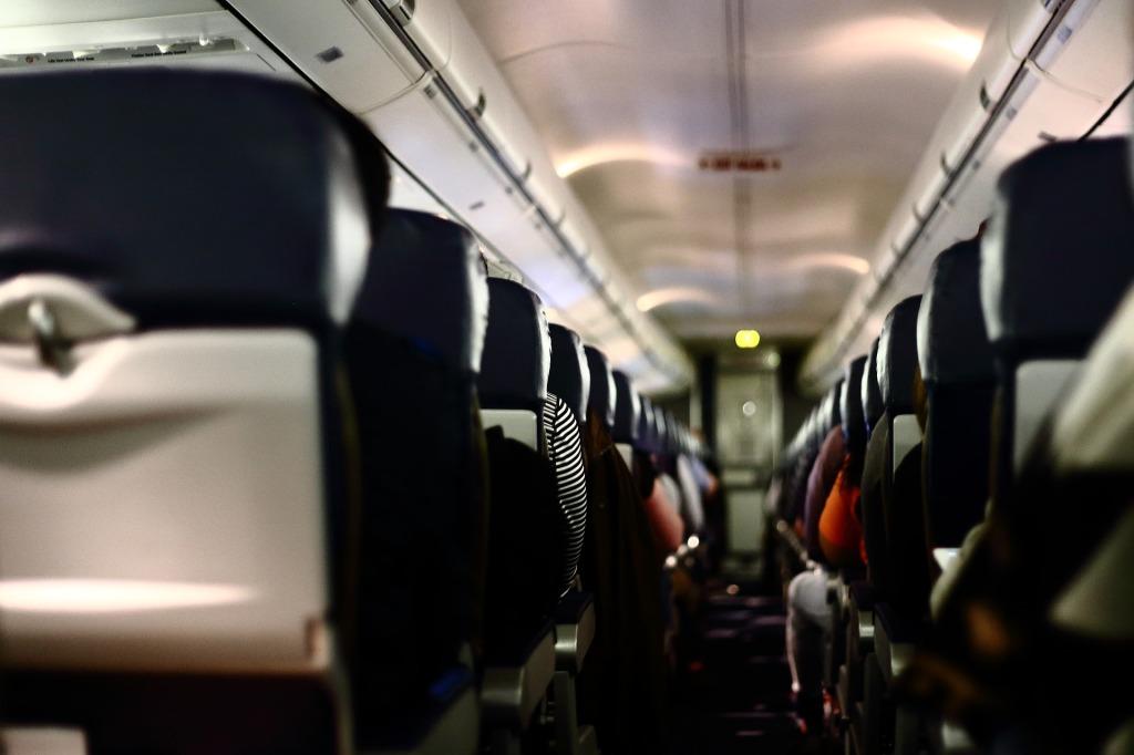 Interior de un avión. No se ven detalles enfocados, solo la mirada desde el fondo del pasillo (parte trasera del avión) y la tanda de sillones a cada lado de la imagen.