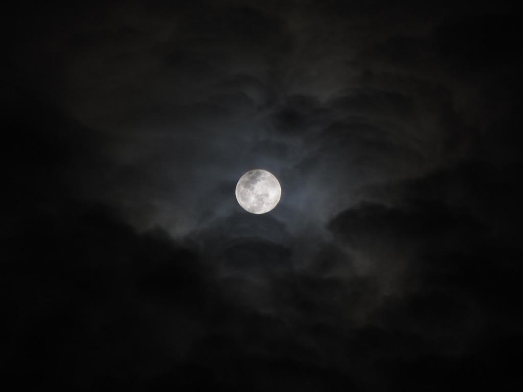 La luna llena viste entre nubes difusas y rodeada de toda la negrura de la noche.